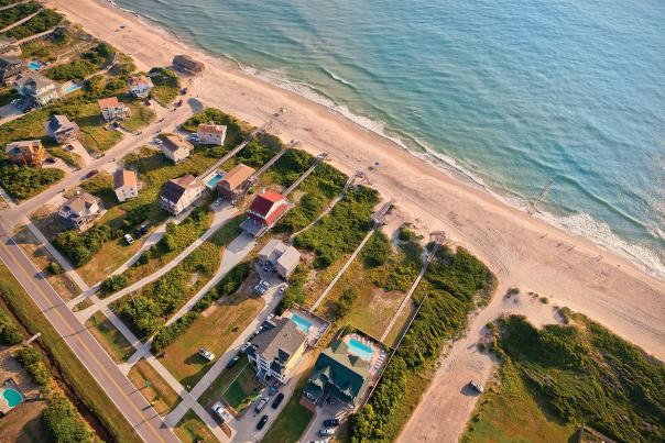 An aerial shot of beach-front rental homes situated on the coast of the Outer Banks in North Carolina.