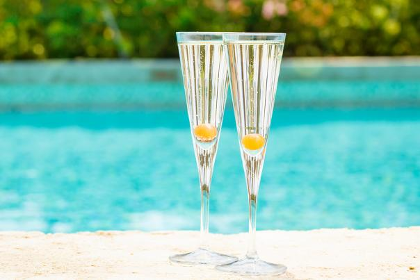 Two Champagne flutes pool side.