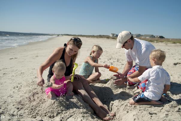 Family building sandcastles on Caswell Beach, NC.