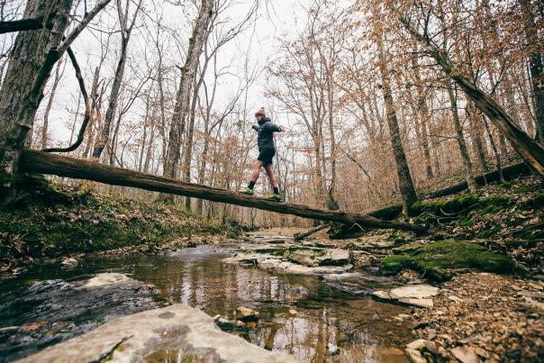 hiker crosses creek on a log at Rotary Park