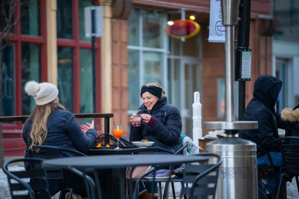 Two women enjoy drinks outdoors in winter