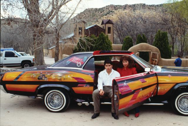"""Dave Jaramillo Jr. and his wife, Irene, with his late father's lowrider, """"Dave's Dream,"""" in front of the Santuario de Chimayó, 1992, New Mexico Magazine"""