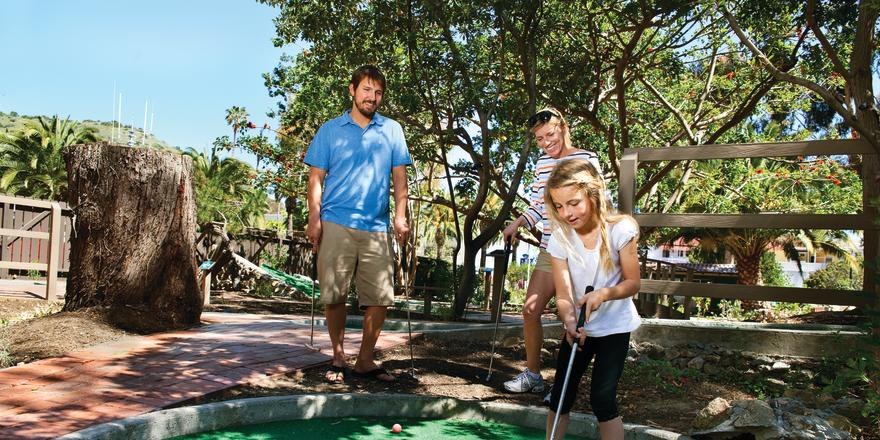 Parents watching child playing mini golf on Catalina Island