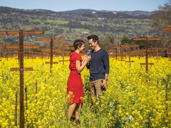 A couple enjoys wine among the wildflowers at Robert Biale Vineyards in Napa Valley