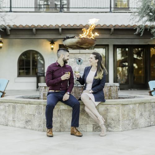 Couple enjoy wine on a romantic patio at Rancho Las Palmas Resort