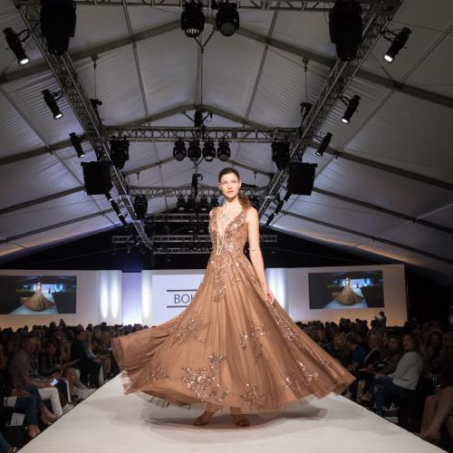A model walks down the runway in a floor-length gown at Fashion Week El Paseo