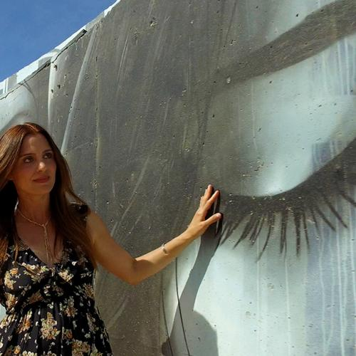 Woman admiring a black and white mural.