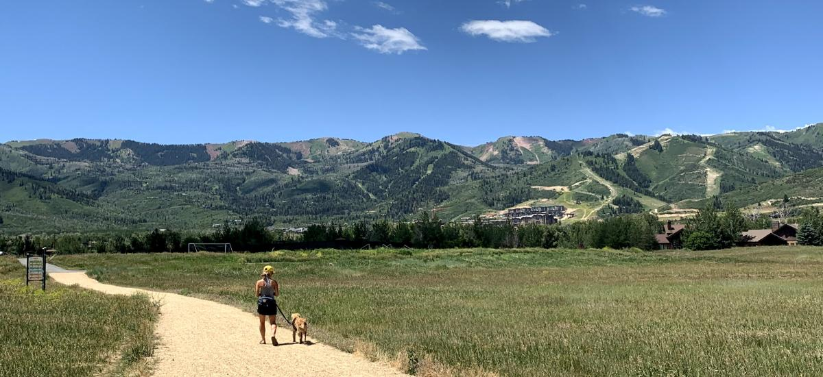 Woman walking with her dog with scenic mountains in background