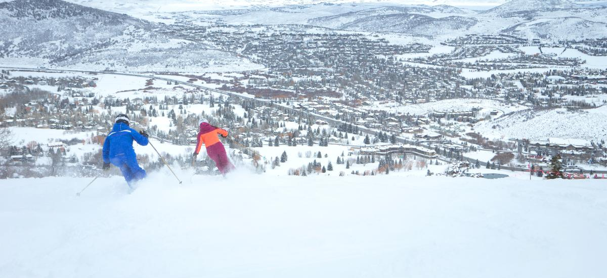 Two people skiing at Park City Mountain with a view of the town in the backgroud
