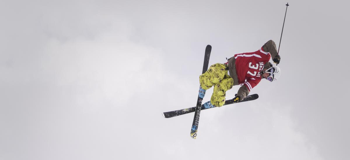 Skier getting big air in a halfpipe over a crowd