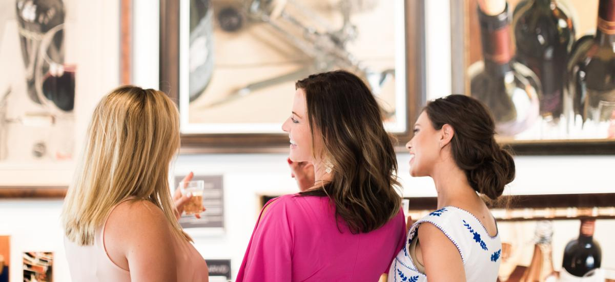 Three women viewing art and talking to each other