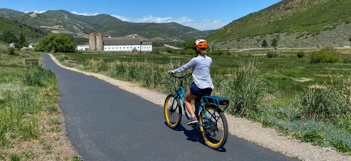 Woman riding an electric bike along a paved path with a white barn in the background