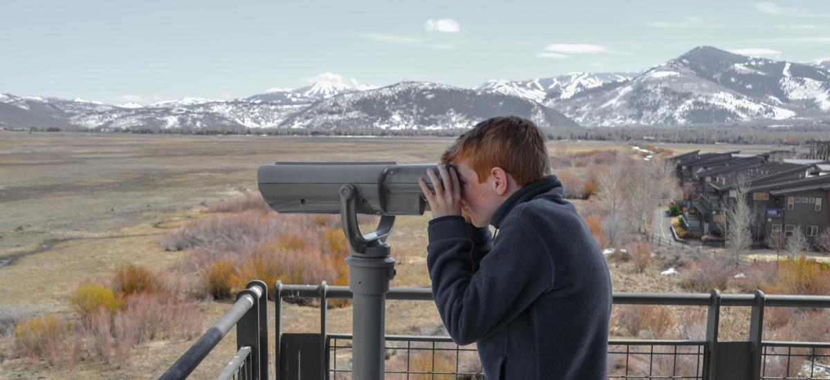 a child looking through binoculars at wetlands