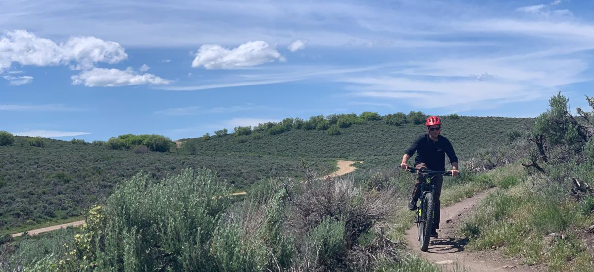 A guy riding a mountain bike with scenic mountain view in background
