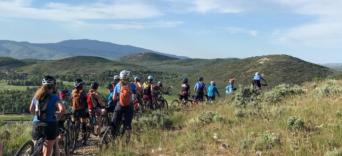 Women on mountain bikes in a line along a trail