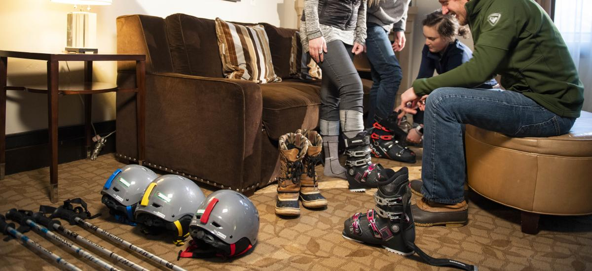 Man helping a women try on ski boots