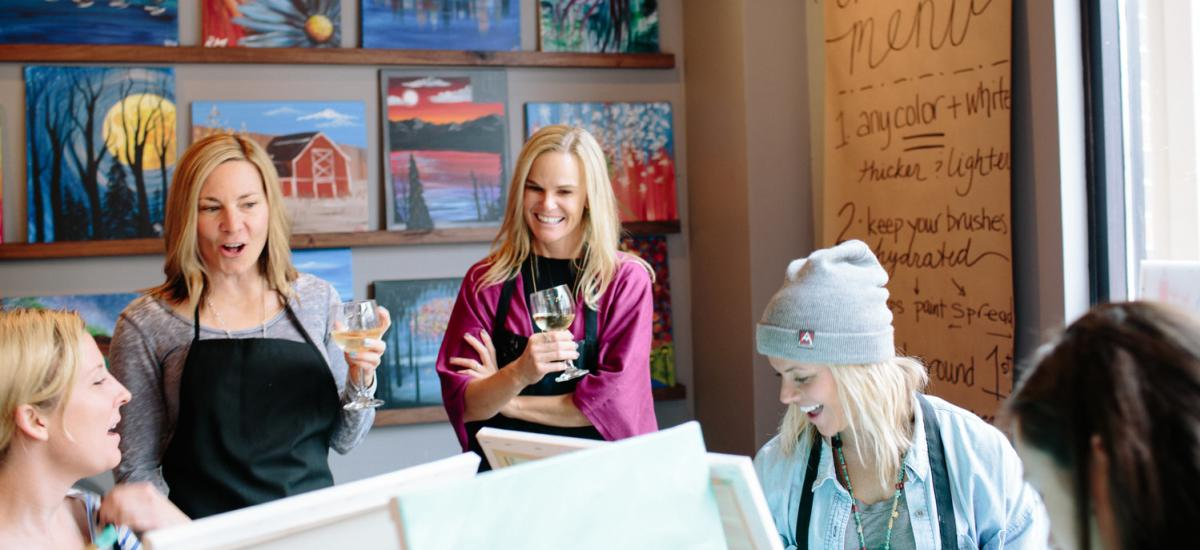 a group of women drinking wine and painting together