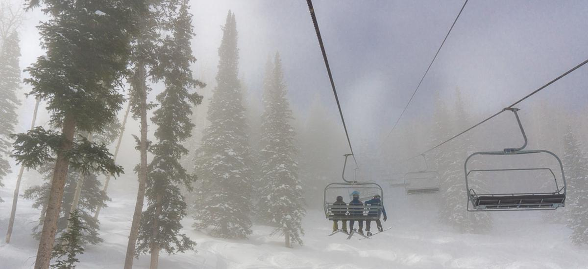 Three people riding up a chairlift through a cloudy morning