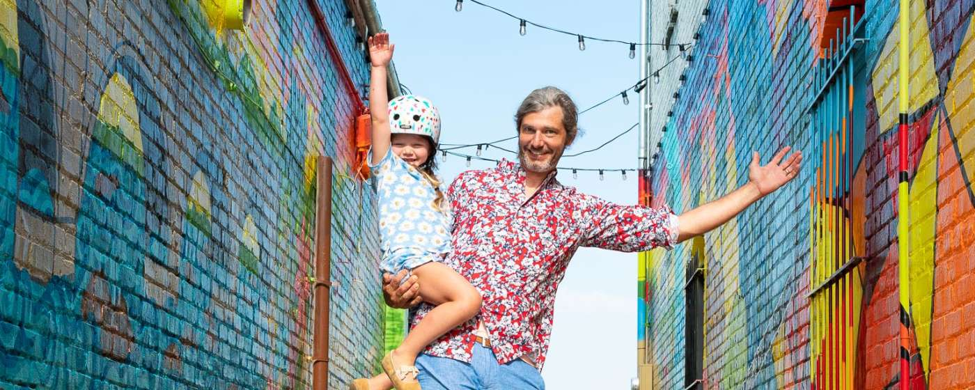 """Dad and daughter skateboarding by """"Alley on State"""" mural in West Columbia (Vagabond3 visit)."""