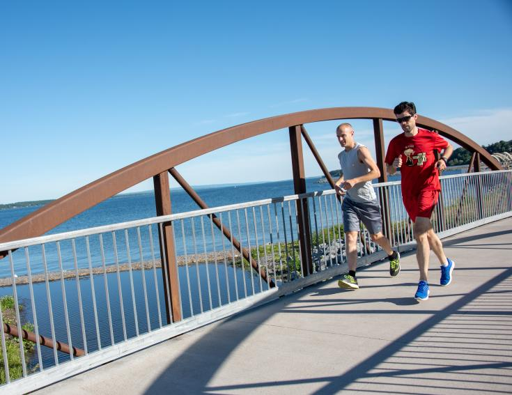 Two men running over a bridge near Seneca Lake