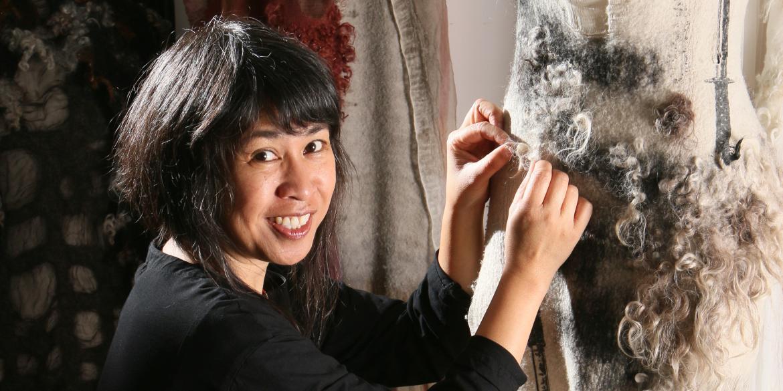 Designer Celeste Malvar-Stewart works on a dress made of sustainable fabrics