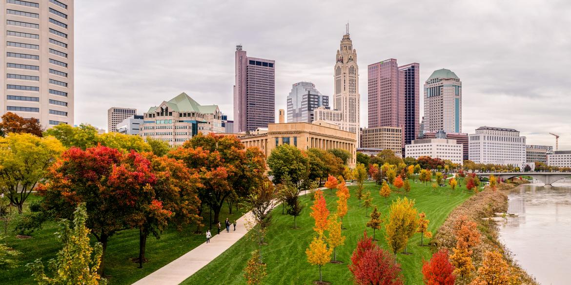 Trees in fall colors on riverfront of Scioto Mile with city skyline in background