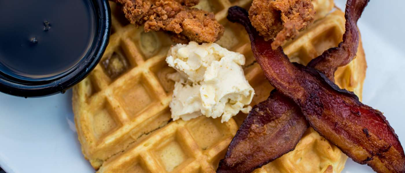 Plate with a waffle, fried chicken and bacon