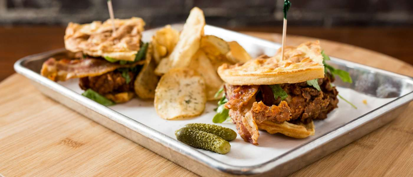 Photograph of a Chicken and Waffles Club Sandwich with potato chips and pickles