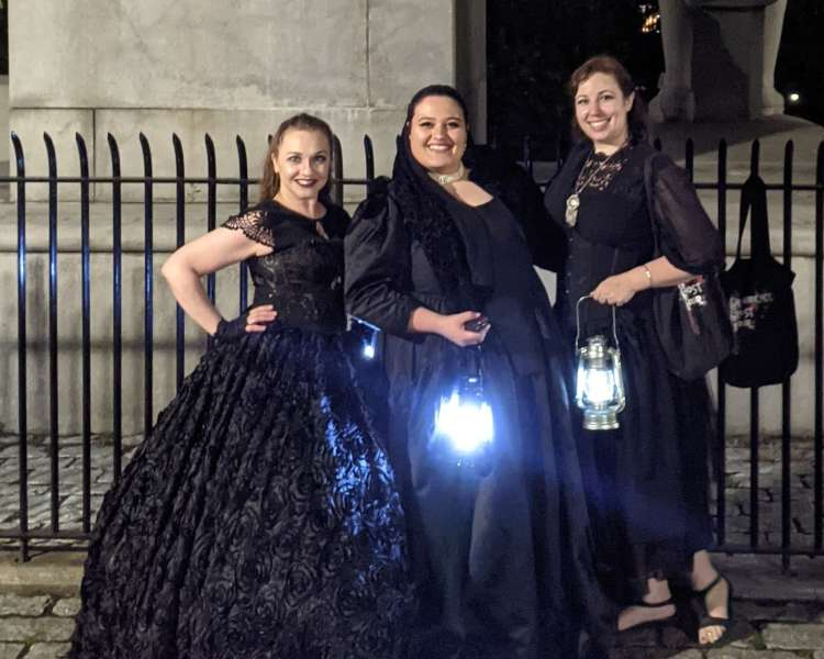 Three female tour guides dressed in period black dresses carrying lanterns.