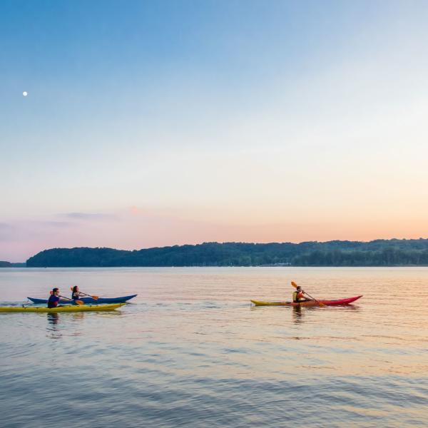 Three kayaks on Monroe Lake during sunset