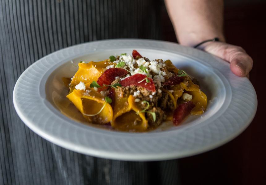 Chef holding pasta dish