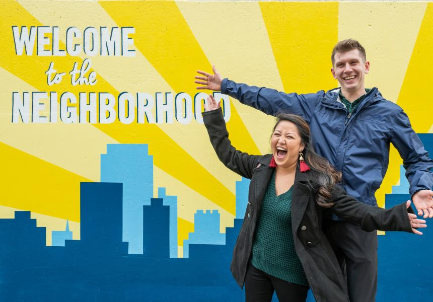 Couple enjoys the Welcome to the Neighborhood mural in the Vista Greenway.