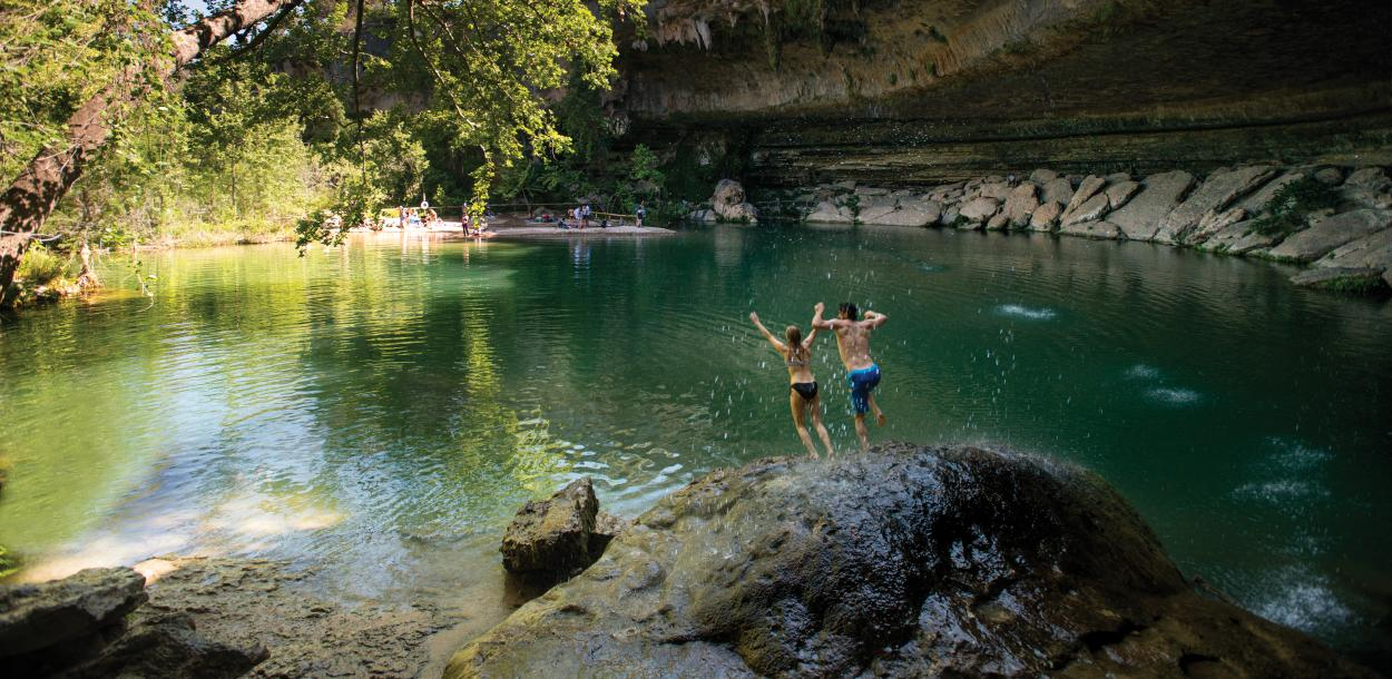 Couple jumping into hamilton pool in dripping springs near austin texas
