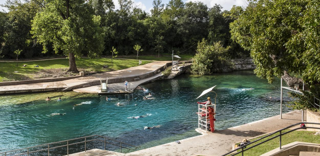 People swimming in Barton Springs Pool with lifeguard in stand