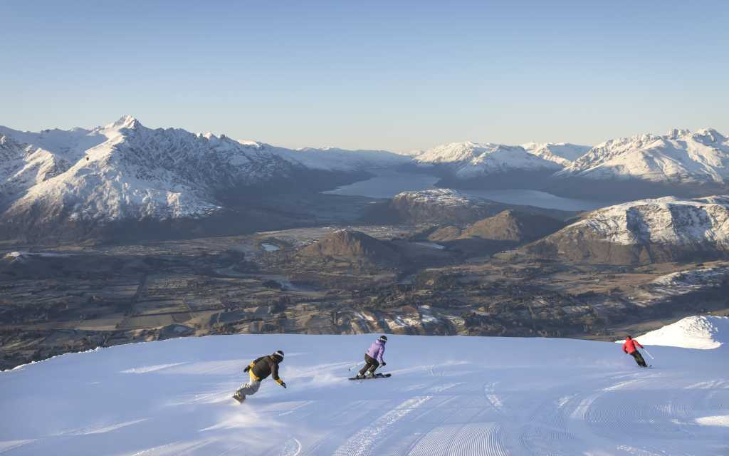 Snowboarding at Coronet Peak with lake and mountains in background