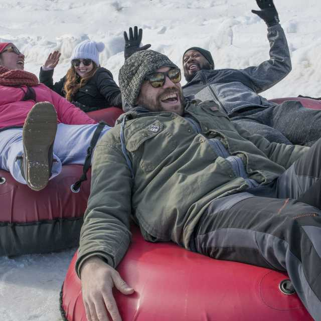 A group of young adults enjoy snow tubing at Roundtop Mountain Resort