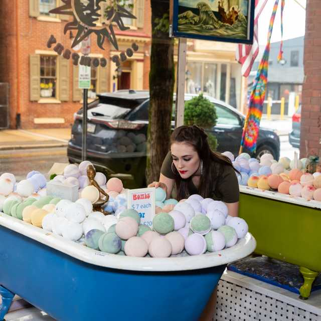Woman leaning over collection of bath bombs