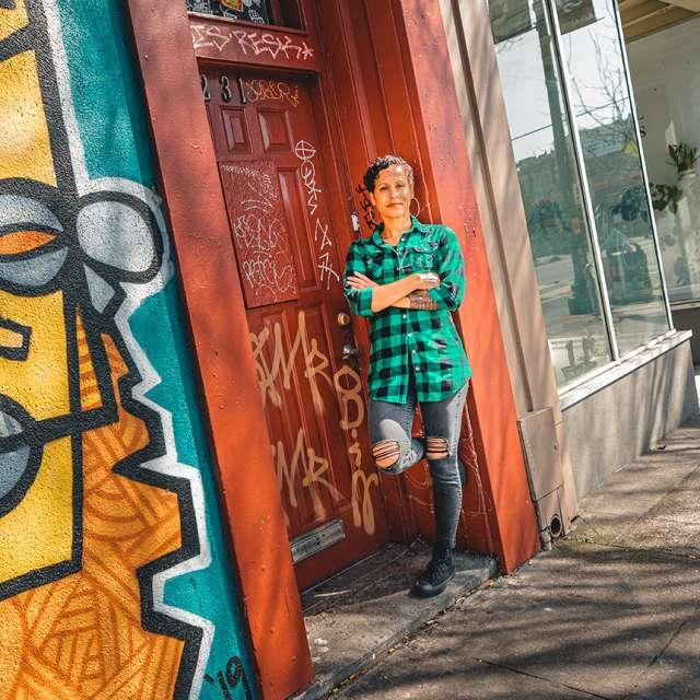 Cava in front of mural in Oakland, CA