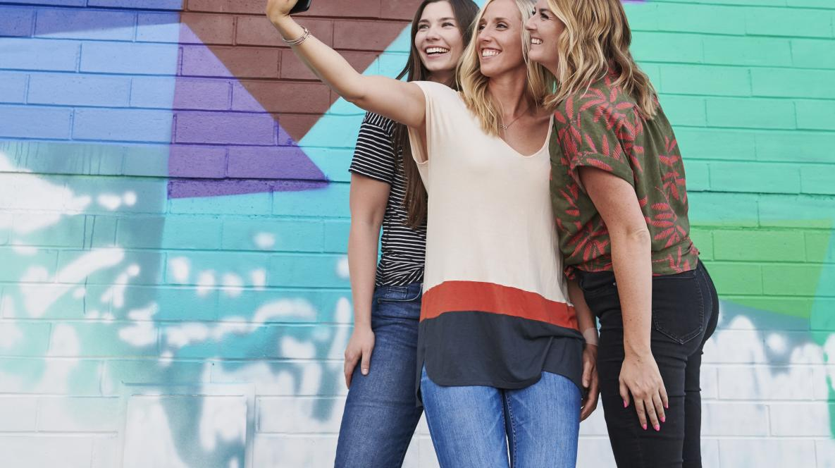 Women Taking Selfie at Colorful Wall in Sandy