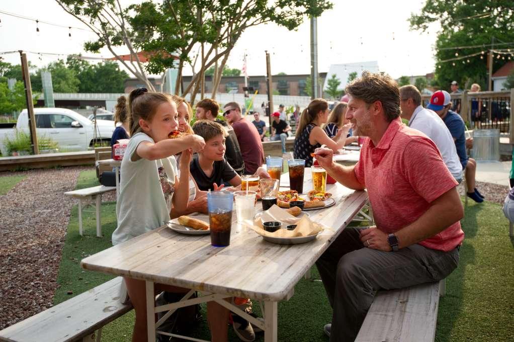 ϾFamily eating pizza and breadsticks on an outdoor picnic table at Parlour in Jeffersonville, IN}}