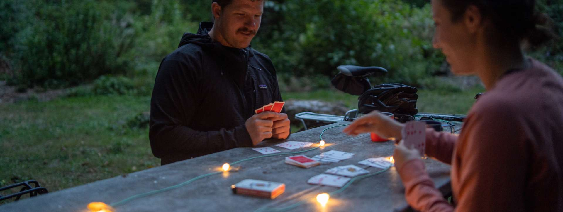 Couple play cards at picnic table in Saltwater State Park