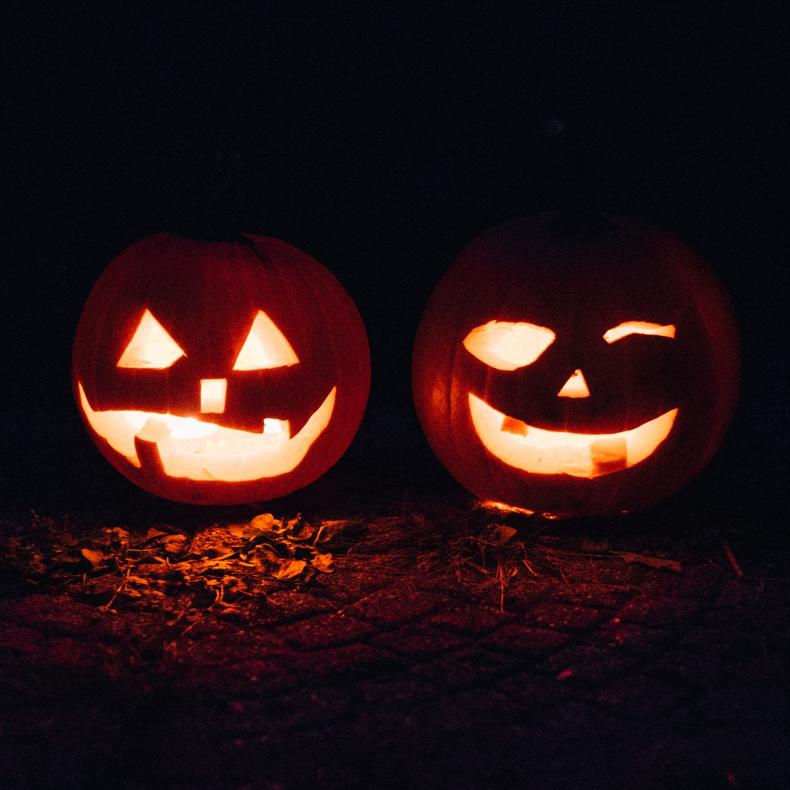 Two jack-o-lanterns glow in candlelight on an October night.