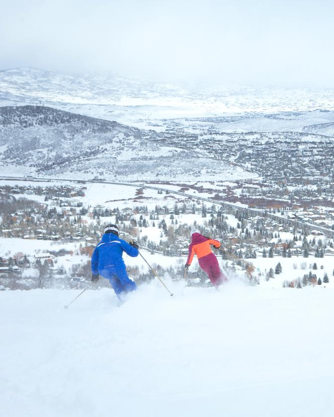 Two people skiing at Park City Mountain with a view of the town in the background