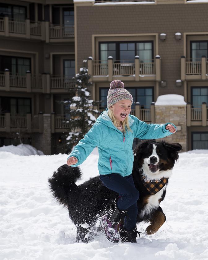 Girl playing the snow with Montage dog ambassador