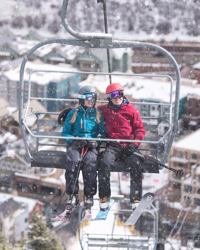 Skier couple on chairlift with town lift plaza in background