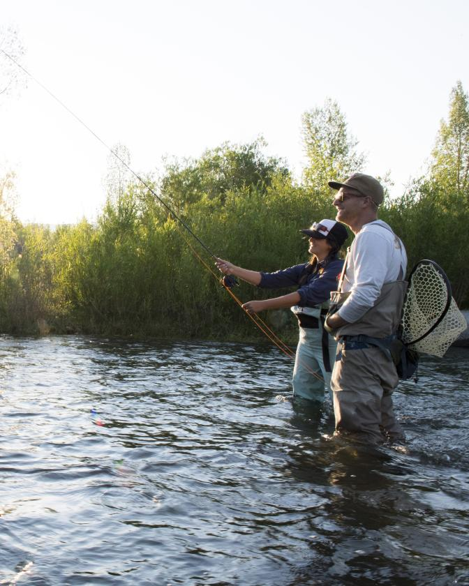 Man and woman fly fishing in the summer on the Provo River.