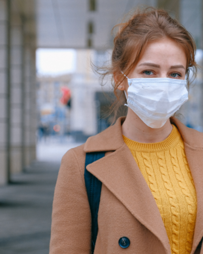 red haired woman with hello sweater and coat wearing and non-surgical mask.