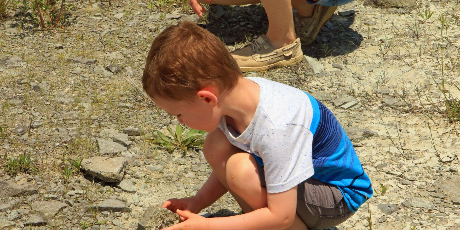 Boy bent down looking at rocks at Caesar Creek Lake