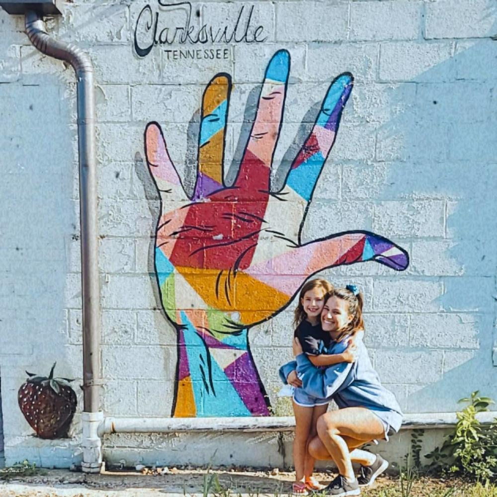 mom and daughter by a colorful mural