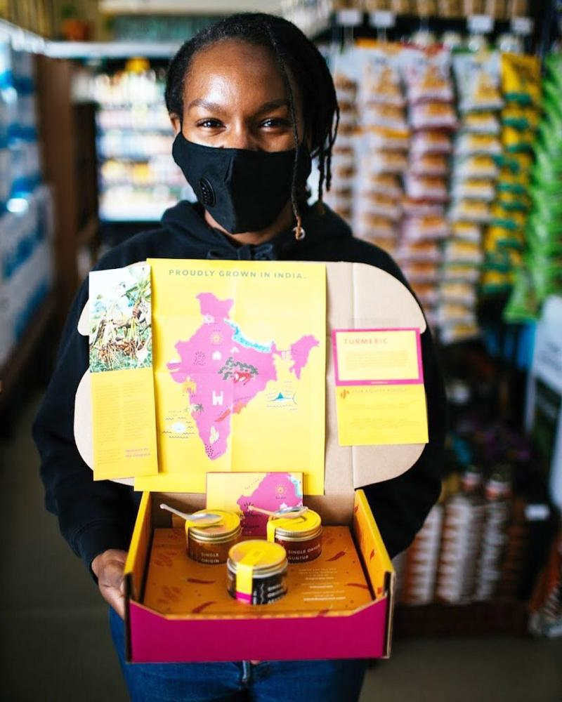 Woman holding a box of products sourced from India at the West Oakland Mandela Grocery COOP